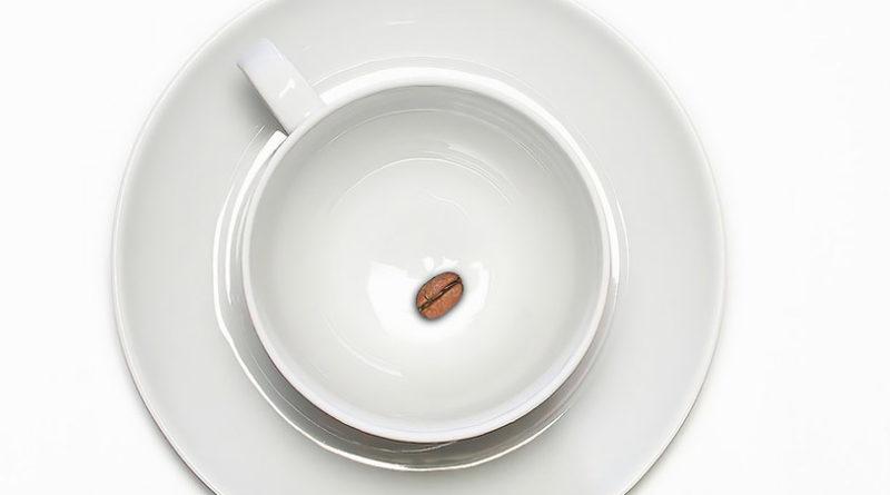 tazzina con chicco di caffè sul fondo